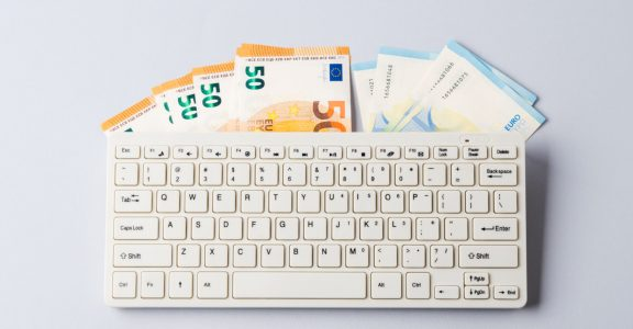 Euro money banknotes under keyboard, online banking, sale of digital info products concept. Financial online investment, trading, income earnings concept, banner