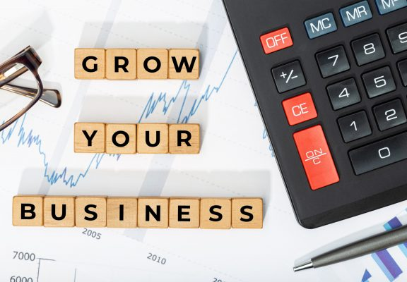 Grow your business concept. Wooden blocks with phrase, calculator and printed chars