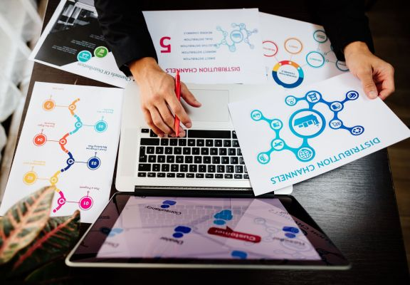marketing manager making marketing distribution channels plan. Marketing manager desk with plans and strategy of distributive channels for new product.