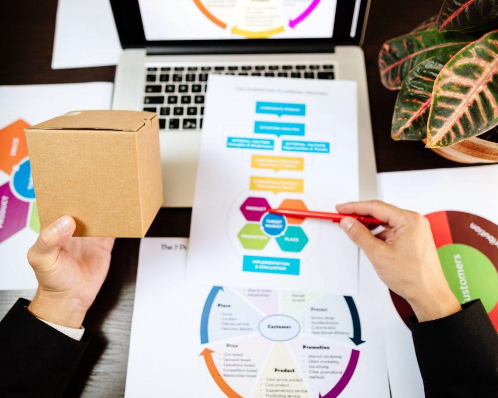 product marketing manager making marketing strategy for new product. Manager holding new product and developing new marketing strategy plan for customers.
